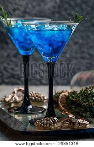 Blue cocktail with ice and rosemary in martini glasses on gray background