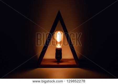 Classic Edison old glowing light bulb with filament in loft lamp standing in wooden triangl as a candle. Abstract background. eco led illuminator at night.