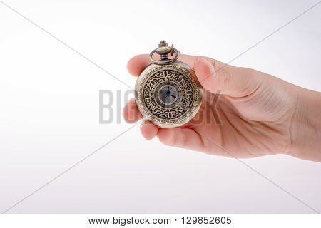 Hand holding a retro styled pocket watch in hand