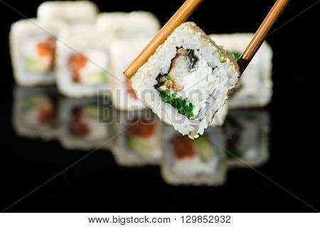 close up of chopsticks taking portion of sushi roll on the table restaurant / eating sushi roll using chopsticks