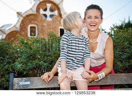 Child Whispering Something To Mother In Park Guell, Barcelona