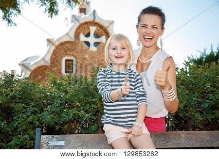 Happy Mother And Child Showing Thumbs Up In Park Guell