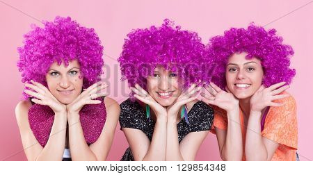 Portrait of a young women wearing a carnival wigs over a pink background.
