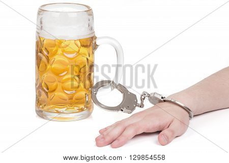 hand handcuffed to a beer mug over white