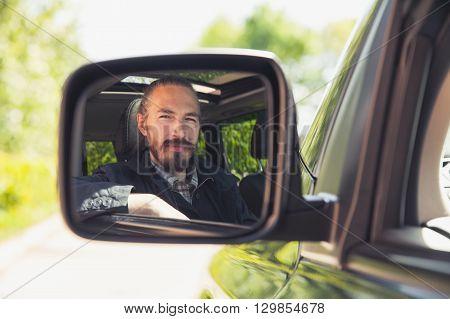 Serious Asian Man As A Driver Looks In Car Mirror