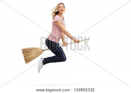 Joyful young woman flying on a broom and looking at the camera isolated on white background