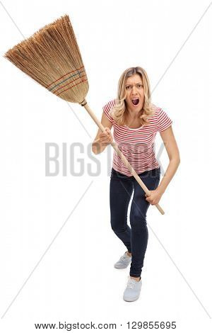 Vertical shot of an angry woman threatening with a broom and shouting towards the camera isolated on white background