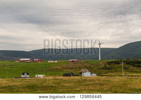 CAPE BRETON CANADA - 27TH AUGUST 2014: Buildings hills and a wind turbine in Cape Breton Nova Scotia during the day