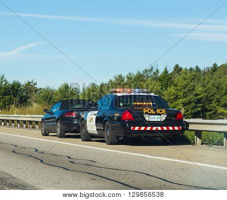 CANADA - 29TH AUGUST 2014: A car that has been pulled over by the police on a road in Canada.