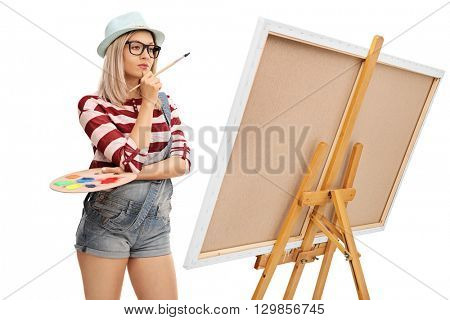 Female artist holding a paintbrush and a color palette and looking at a painting isolated on white background