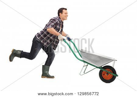 Happy gardener pushing an empty wheelbarrow and running isolated on white background