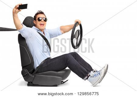 Young man holding a steering wheel and taking a selfie seated on a car seat isolated on white background