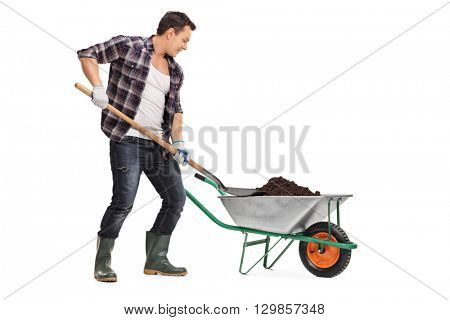 Young worker loading dirt into a wheelbarrow with a shovel isolated on white background