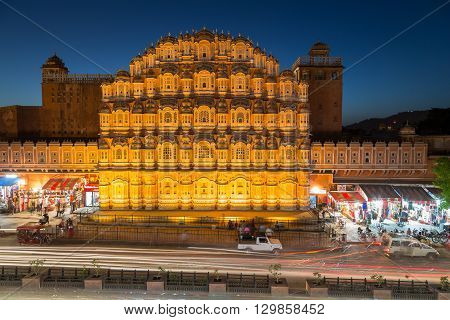 JAIPUR INDIA - 22ND MARCH 2016: A view of the Hawa Mahal (Palace of the Winds) in central Jaipur at night. The blur of traffic and people can be seen outside on the street.