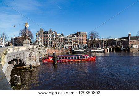 AMSTERDAM NETHERLANDS - 16TH FEBRUARY 2016: A City Sightseeing Boat in the Amsterdam Canals. Passengers can be seen on the boat.