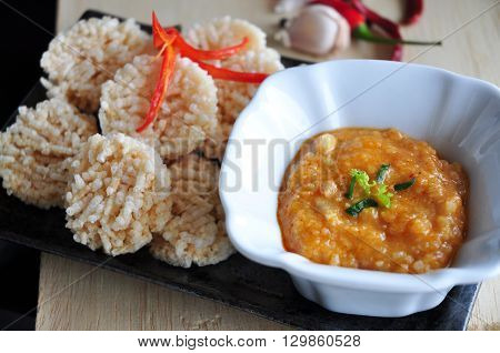 Thai dish dipping sauce with rice cracker on tray