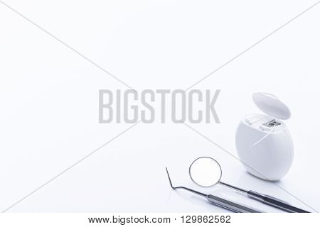 Dental Floss With Basic Dental Tools On A White Table
