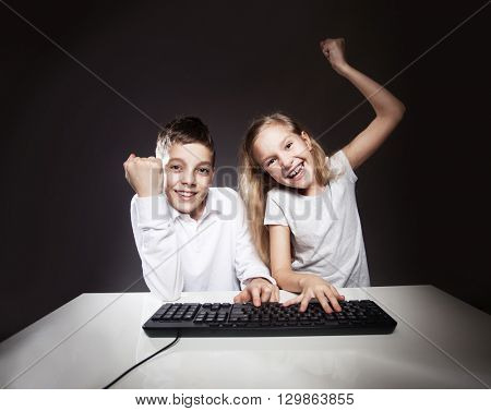 Fun children looking at a computer. Computer addiction