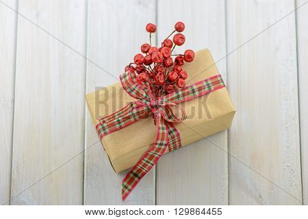 Box with a gift on a wooden table tied with red ribbon and an ornament of red twigs with berries.