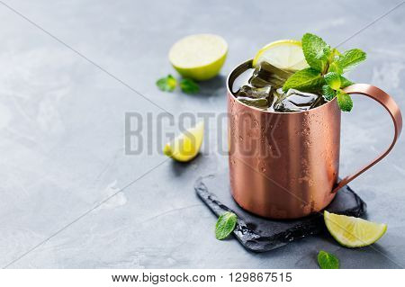 Cold Moscow Mules cocktail with ginger beer, vodka, lime Grey stone background. Copy space