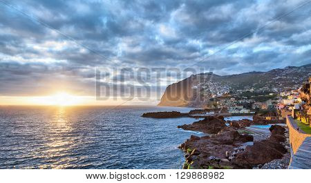 Sunset over Cabo Girao cliff viewed from Camara de Lobos Madeira Portugal