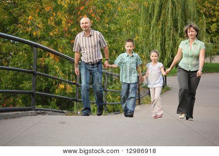 family with two children is handies on a bridge and walking