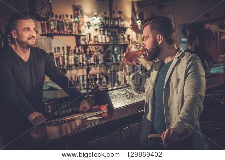 Cheerful stylish man drinking draft beer at bar counter in pub.