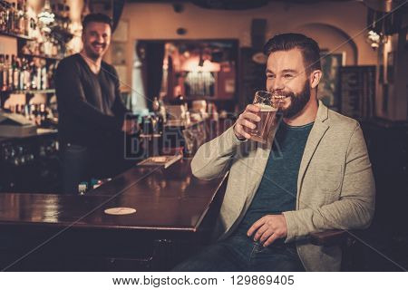 Stylish man paying for beer by cash euro to bartender in pub.