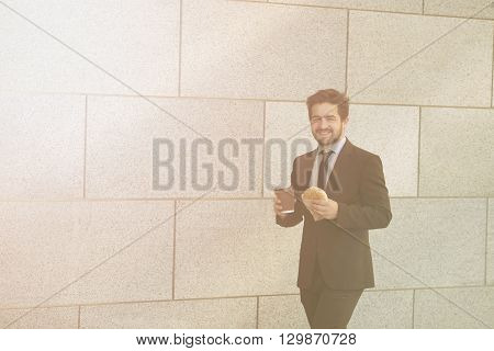 Toned picture of smiling businessman eating junk food and drinkig cupof tea or coffee while walking to office along street.