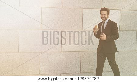 Toned portrait of happy businessman eating junk food and drinking tea or coffee while walking to office along street.