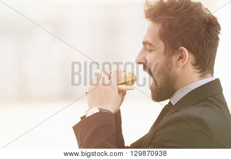 Closeup toned image of handsome businessman or freelancer eating junk food while going to work to office. Business and freelance concepts.