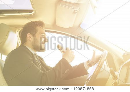 Toned picture of young businessman eating junk food while driving to work. Handsome freelance man looking in front of him.