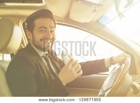 Toned picture of young businessman having coffee and doughnut in his car. Happy freelance man smiling for camera while driving to work.