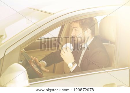 Toned picture of young businessman eating junk food while driving to work to office. Handsome man in black business suit looking to traffic jam.