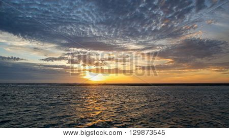 Evening cloudy sunset skies over the Murchison River and river mouth waters in Kalbarri, Western Australia.