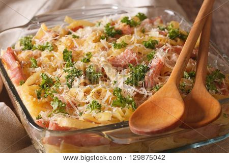 Austrian Noodles Baked With Ham And Parmesan Close-up In A Glass Baking Dish. Horizontal