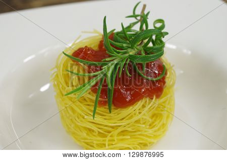 pasta macaroni with spice rosemary on white plate