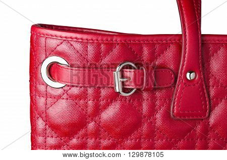 Close up sectioin of woman red leather hand bag showing decorative silver belt buckle isolated white background