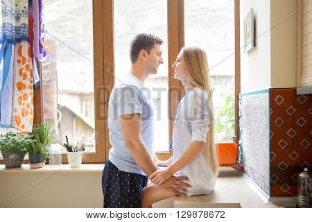 Young happy couple hugging in the kitchen