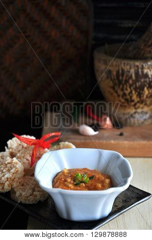 Thai food rice cracker with dipping sauce on tray with mortar on background