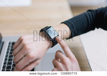 Photo Woman Working Modern loft, Using Generic Design Smart Watch.Female Hands Touching Screen Smartwatch.Account Manage Work Process. Horizontal. Burred background. Film effects.