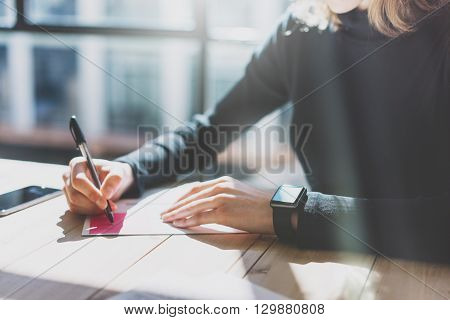 Photo Woman Working Modern Studio, Wearing Generic Design Smart Watch.Female Hands Writing notes. Account Manager Work Process.Smartphone on the Wood Table.Horizontal, Burred Background. Film effects.