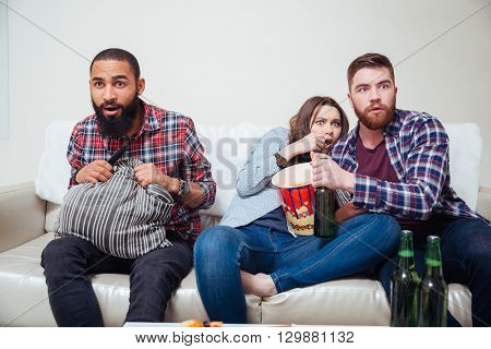 Three scared young friends sitting on sofa and watching tv