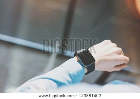 Picture Woman Working Modern Loft Studio.Girl Enjoying Generic Design Smart Watch.Looking Screen Smartwatch.Using Free Time Management. Horizontal mockup. Burred background. Film and bokeh effects.