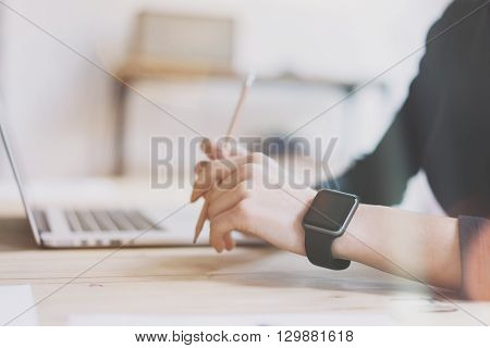 Photo Girl Working Modern Laptop in Studio Loft. Woman Wearing Generic Design Smartwatch.Account Manager Work Process. Notebook on the Wood Table.Horizontal mockup.Burred background. Visual effects.