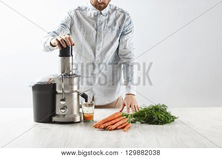Focused On Carrots. Unrecognizable Man Presses Carrots Inside Metallic Professional Juicer To Make T