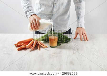 Unrecognizable Man Pours Milk From Bottle To Transparent Glass With Freshly Pressed Natural Carrot J
