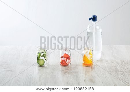Rustic Jars With Ice And Various Fillings: Orange,strawberry,cucumber And Mint Prepared To Make Fres
