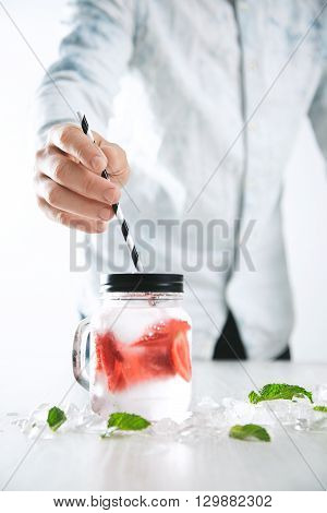 Bartender Puts Striped Drinking Straw In Jar With Fresh Cold Homemade Lemonade Made From Ice, Strawb