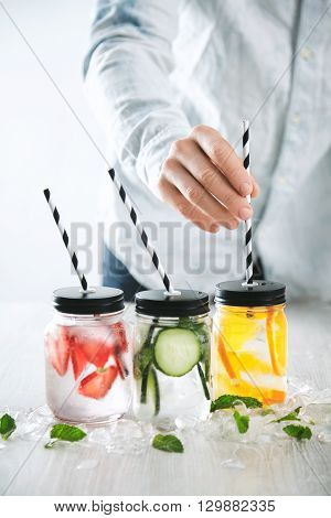 Bartender Puts Striped Drinking Straws In Jars With Fresh Cold Homemade Lemonades Made From Ice, Str